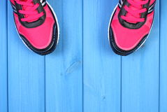 Pair of pink sport shoes on blue boards background, copy space for text Stock Photos