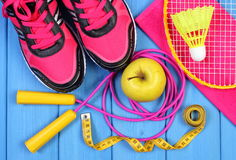 Pair of pink sport shoes, fresh apple and accessories for sport on blue boards Stock Photos