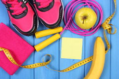 Pair of pink sport shoes and fresh fruits on blue boards, copy space for text on sheet of paper Royalty Free Stock Photo