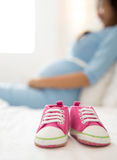 A pair of pink toddler sneakers beside a pregnant woman, focus o. A portrait of a pair of pink toddler sneakers beside a pregnant woman, focus on the sneakers royalty free stock photos