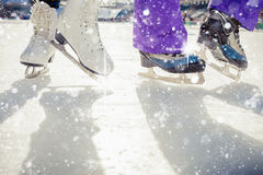 Pair is placed on ice skating. It is snowing outside. Skating close-up. Medeo, Kazakhstan Royalty Free Stock Photo