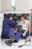Pair of plumbers fixing the pipe of the kitchen Royalty Free Stock Photography