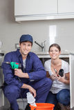 Pair of plumbers working happily Royalty Free Stock Image