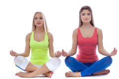 Pair of pretty young girls meditates in studio Stock Photography