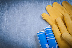 Pair of protective gloves blue rolled construction drawings Royalty Free Stock Photo