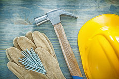 Pair of protective gloves claw hammer nails building helmet on w Royalty Free Stock Photography