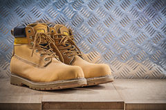 Pair of protective waterproof boots wooden board grooved metal s. Heet construction concept Stock Photos
