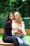A pair of proud lesbian in outdoors sitting on a wooden table, brunette woman is hugging a blonde woman, in a garden stock photos