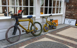 A pair of push cycles, one with bull horns and covered with knitting outside a craft shop in Londonderry. These push bikes covered with unusual knitting and Royalty Free Stock Photo