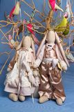 A pair of rabbits stand on a tree background with birds, toys. Toys, bunnies, rabbits, handmade on a tree background with birds, toys Stock Image