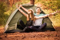 Pair raised their hands up to sunlight on forest near tent. Concept of active vacation in camping. Pair raised their hands up to sunlight on green forest near royalty free stock photo