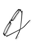 Pair of reading glasses or spectacles. With modern dark frames folded up on a white background, view from above Royalty Free Stock Image