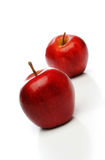 A pair of red apples. A pair of delicious red apples, one on front and one backwards whith a soft lighting over a white background. Look at my gallery for more royalty free stock photography