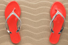 Pair of red beach sandals in rhinestones stand on the sand. Royalty Free Stock Photo