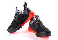 Pair of red & black sporty shoes for kid on white background. Pair of red and black sporty shoes for kid on white background royalty free stock images