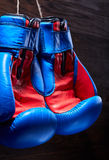 A pair of red and blue boxing gloves hang against wooden wall. Vertical photo of the bright colorful sportwear against brown background. Boxing backgrounds and Stock Photo
