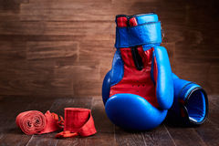 Pair of red and blue boxing gloves and red bandage on brown plank. Horizontal photo of colorful boxing accessories against wooden background. Boxing Stock Photography
