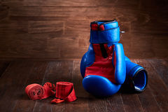 Pair of red and blue boxing gloves and red bandage on brown plank. Horizontal photo of colorful boxing accessories against wooden background. Boxing Stock Image