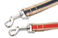 A pair of red and blue striped canvas belt pet collars with snap clasp hook trigger belt clips. A photo taken on a pair of red and blue striped canvas belt pet royalty free stock photo