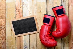 Pair of red boxing gloves with a chalkboard on wooden wall Royalty Free Stock Photography