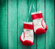 Pair of red boxing gloves hanging on a nail on a background of g Stock Photos