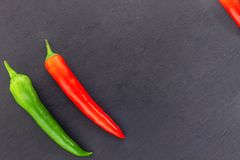 Pair red bright pod hot chili peppers green oblique vegetable corner on a black background royalty free stock images