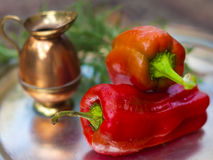A pair of red capsicum annuum (bell peppers). A pair of red capsicum annuum (bell peppers) and a small copper jug royalty free stock photos