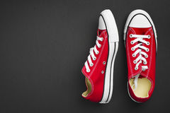 Pair of red classical gymshoes  on dark background Stock Photos