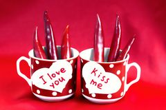 A pair of red cups in polka dots stand on the table. Two white h. Earts made of paper with text I love you and kiss me. Hot peppers like hot love. Valentine`s royalty free stock photos