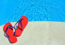 Pair of red flip-flops. Pair of red flip-flops on the swimming pool royalty free stock photo