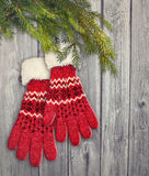 A pair of red gloves hanging on wooden background Royalty Free Stock Images