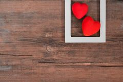 Pair of red hearts in white frame on vintage wooden table, top view. Saint Valentines day background. Pair of red hearts on vintage textured wooden table with stock images