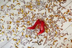 Ladies shoes. Pair of red high-heeled stylish female shoes on white wooden floor covered by confetti stock photo