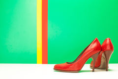 Pair of red high heels. On green and stripes background Stock Photos