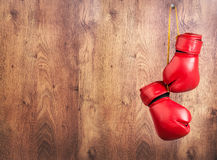 Pair of red leather boxing gloves hanging on a nail on a wooden wall. Wooden wall.Pair of red leather boxing gloves hanging on a nail royalty free stock image