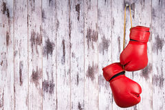Pair of red leather boxing gloves hanging on a nail on a wooden wall. Pair of red leather boxing gloves hanging on a nail royalty free stock images