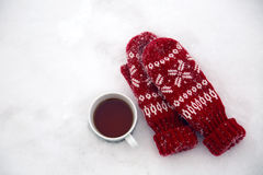 Pair of red mittens lie on the snow Stock Photos