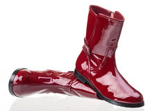 Pair of red patent leather female boots. Over white royalty free stock photography