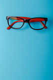 Pair of red plastic-rimmed eyeglasses Stock Photos