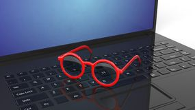 Pair of red round-lens eyeglasses set on laptop Royalty Free Stock Photos