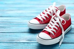 Pair of red sneakers. On blue wooden table royalty free stock photo