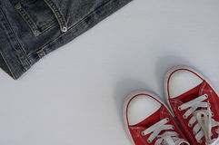 Pair of red sneakers and a fragment of blue jeans on a white woo Stock Images