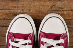 Pair of red sneakers on old retro wooden background stock photo