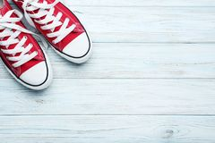 Pair of red sneakers. On white wooden table stock photos