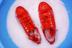 Pair of red sneakers in plastic basin with suds,. Closeup Royalty Free Stock Photos