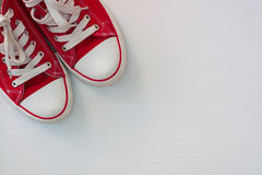 Pair of red sneakers youth on a white wooden surface. Empty space stock photos