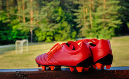 Pair of red soccer shoes with grass field in the background. Pair of red soccer shoes with football field in the background Royalty Free Stock Image