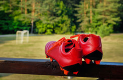 Pair of red soccer shoes with grass field in the background. Pair of red soccer shoes with football field in the background Royalty Free Stock Photos