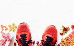 Pair of red sport shoes with Christmas decoration items and pres stock photos