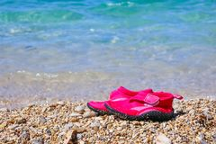 Pair of pink swimming shoes on marble pebble beach beside turquoise sea water. Summer holiday concept. Kids shoes for. Pair of red swimming shoes on marble Royalty Free Stock Photography